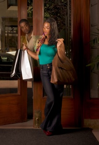 African-American woman getting in building - man looking on her